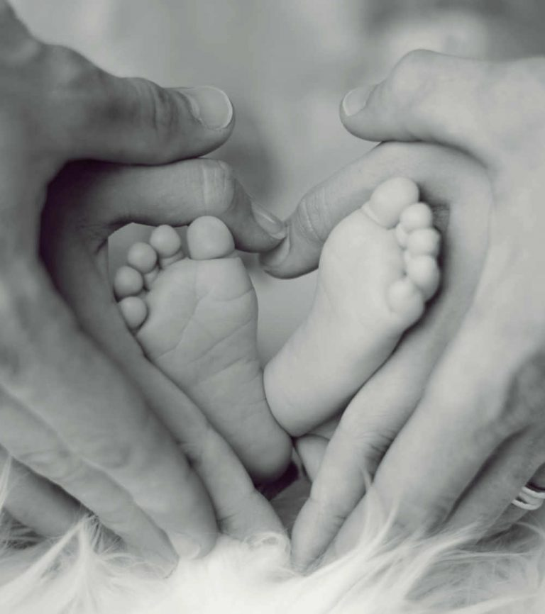 Photo of baby feet held by parents hands