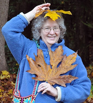 senior woman having fun with maple leaves