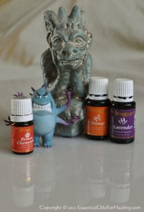 toy monster and gargoyle with bottles of relaxing essential oils