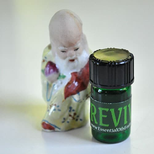 REVIVE™ essential oils blend with ceramic Chinese philosopher figurine