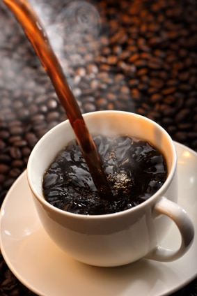 photo steaming hot coffee being poured into cup with coffee beans background