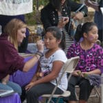 young chinese sisters getting face painted