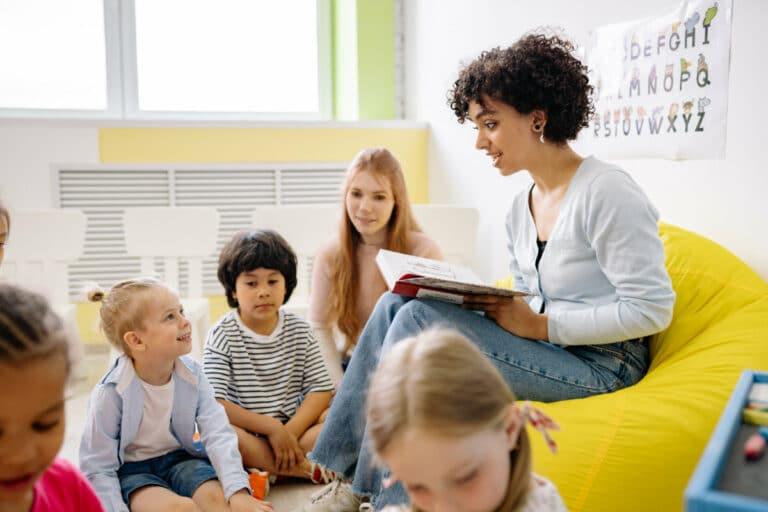 young woman teacher reading to kindergarten students